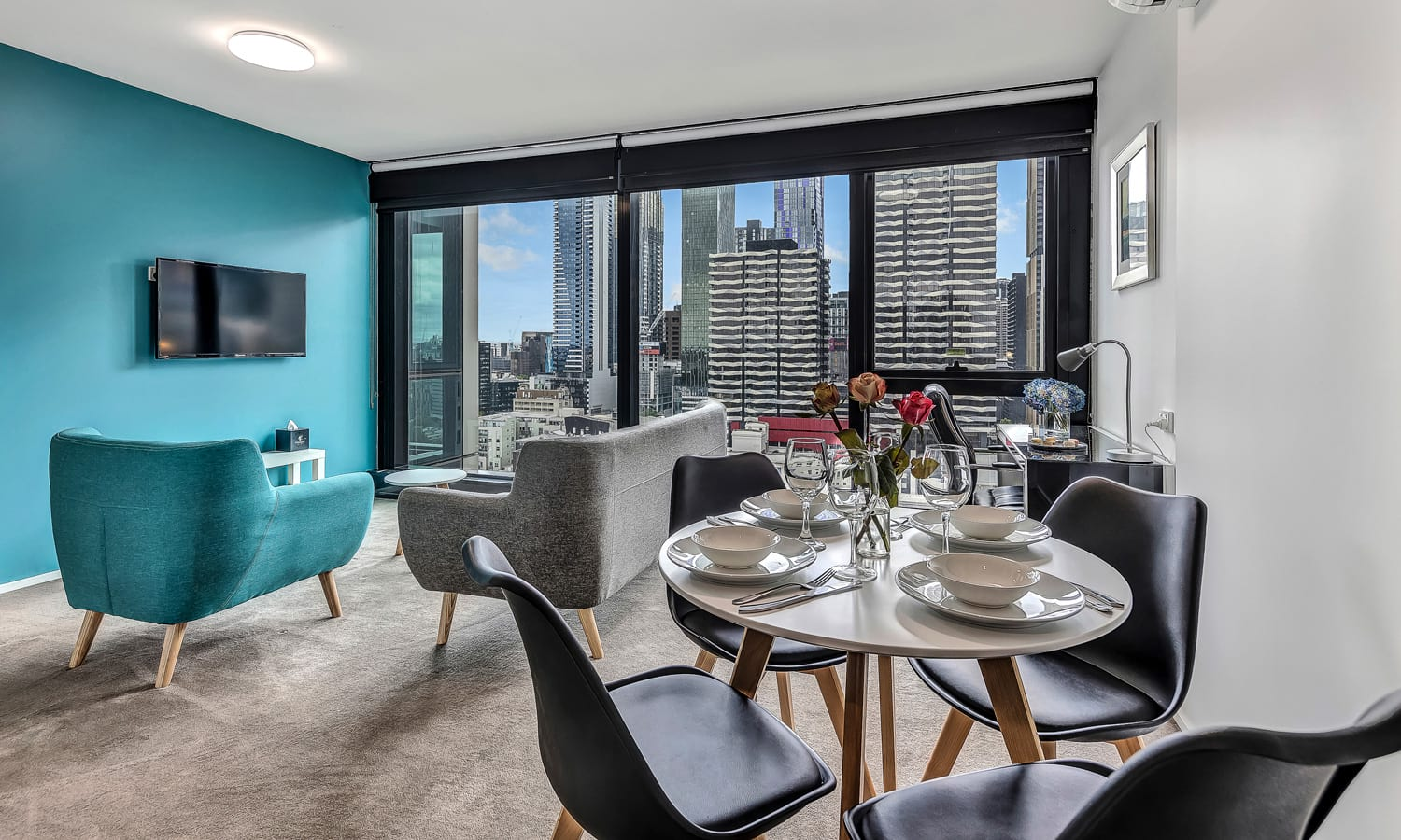 dining and lounge area with city view in large windows in two bedroom apartment